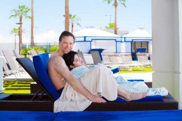 Caucasian father holding disabled son on blue poolside lounger, drying off after swimming. Child has cerebral palsy.