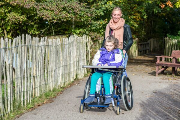 Disability a disabled child in a wheelchair with a care assistant going out for a walk together.